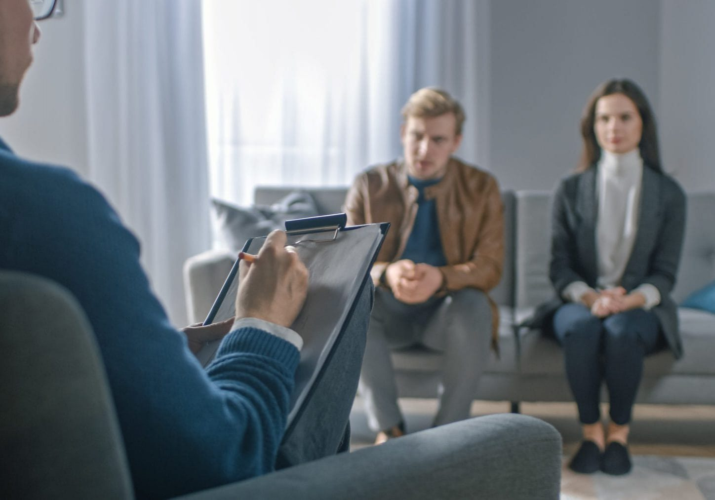 Couple on a Counseling Session with Psychotherapist. Foreground Focus on Back of the Therapist Taking Notes and Talking: People Sitting on the Analyst Couch, Discussing Psychological Problems